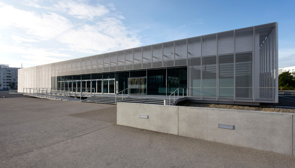 Ein großer, flacher Glasbau auf einer Betonfläche